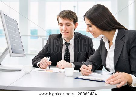 Successful businessman and young businesswoman at office