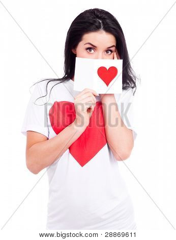 beautiful young woman wearing a T-shirt with a big red heart and holding a Valentine's card in her hand, isolated against white background
