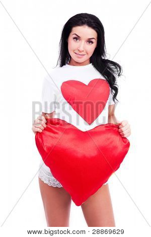 sexy smiling young  woman wearing a T-shirt with a big red heart and holding a heart-shaped pillow, isolated against white background