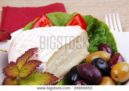 aged camembert cheese on green salad in white dish over cloth with olives and over wooden table