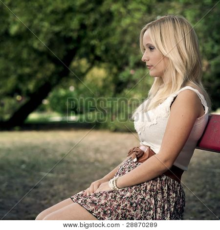 Beautiful young woman sitting on a park bench  and thinking on something