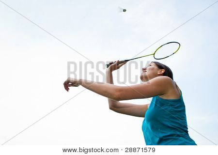 Pretty, young woman playing badminton in a city park on a lovely summer day (shallow DOF)