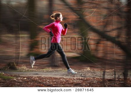 Young woman running outdoors in a city park on a cold fall/winter day (motion blurred image; color toned image)