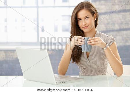 ¿Retrato de mujer sonriente con ordenador portátil, sosteniendo la taza de café, mirando a cámara feliz.?