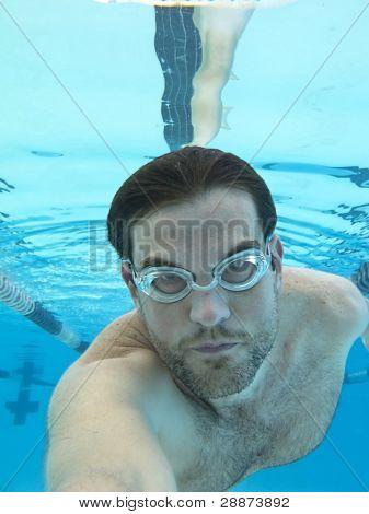man swimming underwater, shot from below surface