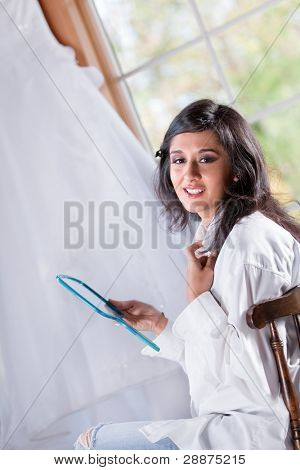 Smiling bride getting ready holding the mirror in front of window with wedding gown hanging background