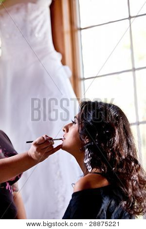 Smiling bride getting ready getting makeup  in front of window with wedding gown hanging