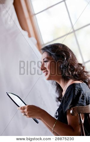 Smiling bride getting ready looking at mirror in front of window with wedding gown hanging