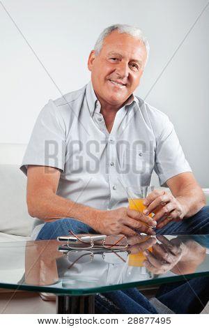 Retrato de hombre senior casual con vaso de jugo de naranja