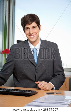 Portrait of smiling male manager sitting at his desk in office
