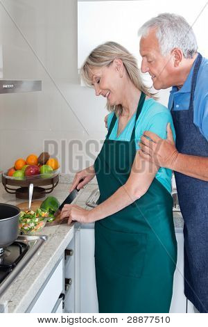 Senior couple cooking food in kitchen at home
