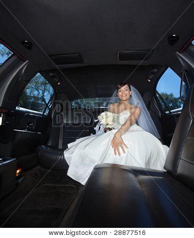 Attractive bride sitting in limousine holding flower bouquet