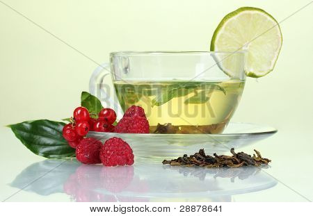 green tea in transparent cup with lime and berry on yellow background