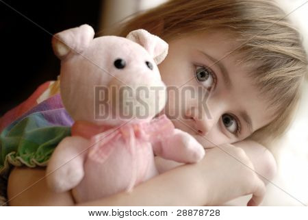 Portrait of young little girl holding stuffed animal with focus on eyes