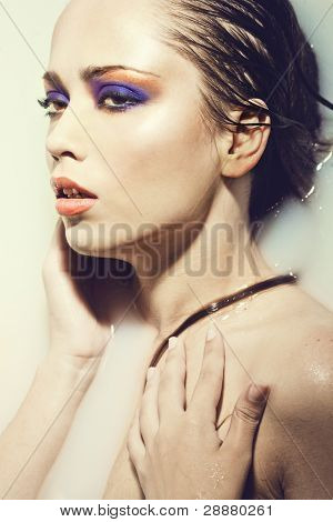 Close-up fine art portrait of a beautiful sexy young woman with creative eye makeup in water