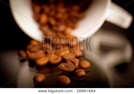 Macro shot of coffee beans from coffee cup on the reflective black background