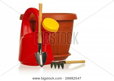 Garden plastic pot, plastic red watering can, spade and rake on a white background