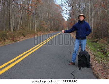 Man Hitchhiking On A Country Road