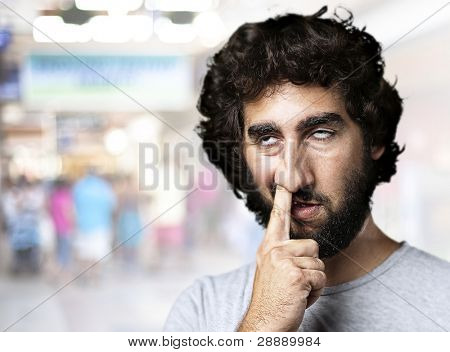 young man with finger in his nose at a crowded place