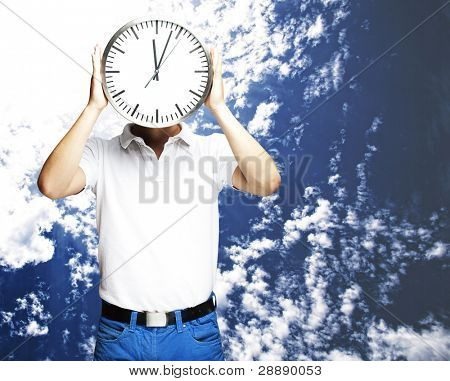 portrait of man holding clock against a cloudy sky background