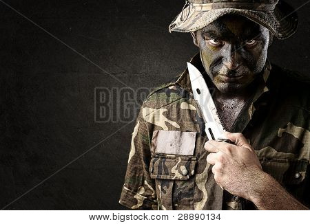 portrait of young soldier treating to suicide against a grunge wall