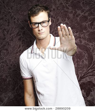 portrait of young man doing stop symbol against a vintage wall