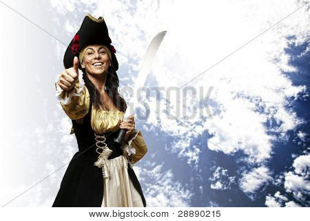 portrait of pirate woman holding a sword and gesturing ok against a cloudy sky background