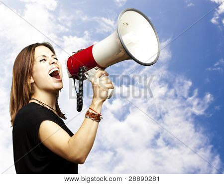 portrait of young woman shouting with megaphone against a blue background