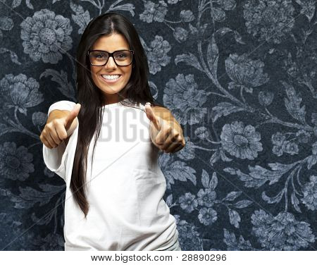 portrait of a pretty young woman doing good symbol against a vintage wall