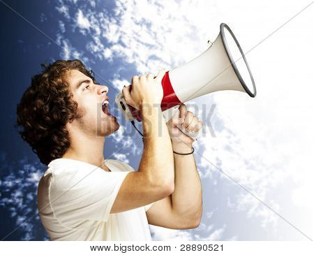 portrait of a handsome young man shouting with megaphone against a cloudy sky background