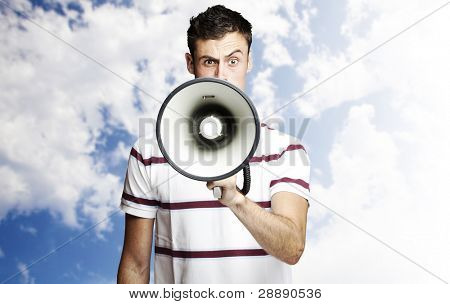 portrait of young man shouting using megaphone against a blue sky background