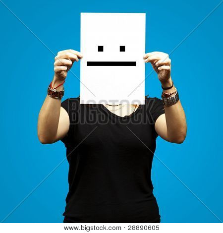 woman holding paper with poker face emoticon against a blue background