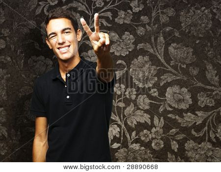 portrait of young man smiling and doing good symbol against a vintage wall