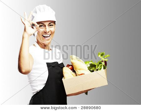 portrait of middle aged woman carrying groceries in a box over grey