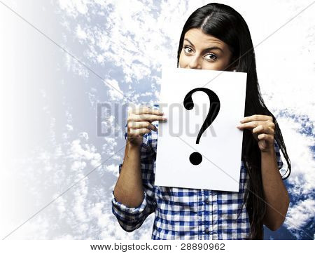 portrait of young woman holding question symbol against a blue sky background