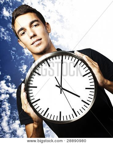 portrait of young man holding a clock with his hands against a cloudy sky background