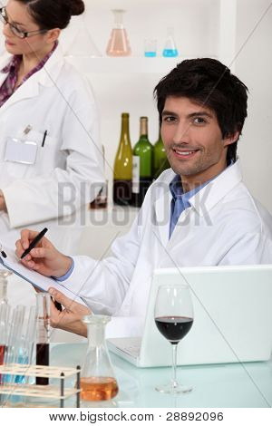 Man and woman conducting experiment on wine
