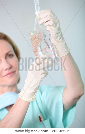 Closeup of a nurse in scrubs administering drip