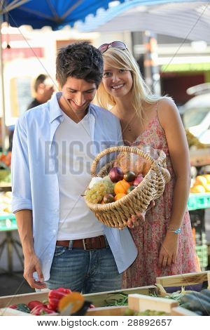 Couple with a basket at market