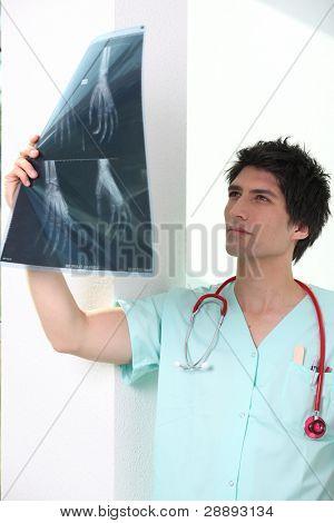 Male nurse holding up x-ray image
