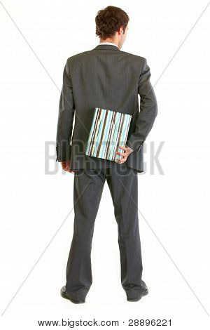 Modern Businessman Hiding Present Behind His Back And Standing Back To Camera