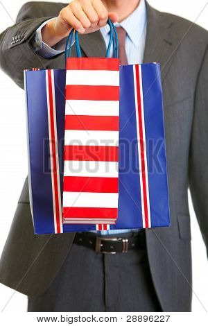 Closeup On Shopping Bags In Hands Of Man In Suit