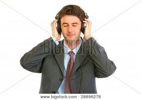 Happy Man In Business Suit Listening Music In Headphones