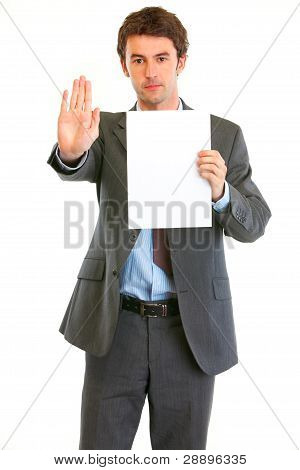 Serious Modern Businessman Holding Blank Paper And Showing Stop Gesture