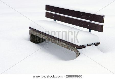 bench under snow winter park
