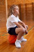 Side view of a mixed -race schoolgirl sitting on a basketball in basketball court at school poster