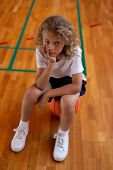 High angle view of a mixed -race sad school girl sitting on basketball and looking at the camera whi poster