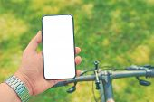 Man With A Smartphone On A Bike Workout On Offroad. Mock Up poster