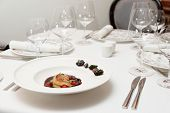 Foie gras dish with red porto sauce and berries, formal restaurant setting poster