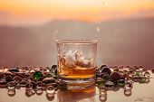 A Glass Of Whiskey With Ice And Gold Sunlight. Outdoor Shot Of Whiskey With Splash On Sunset Backgro poster